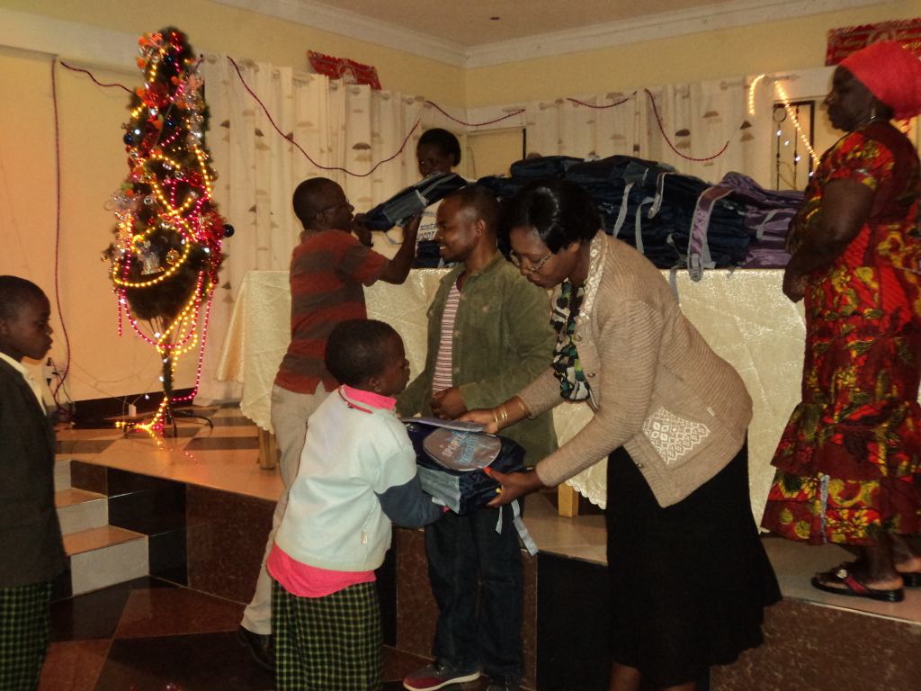 Guest of the hotel owner, Lilian Nyemele, distributing KWA gifts to OVCs.
